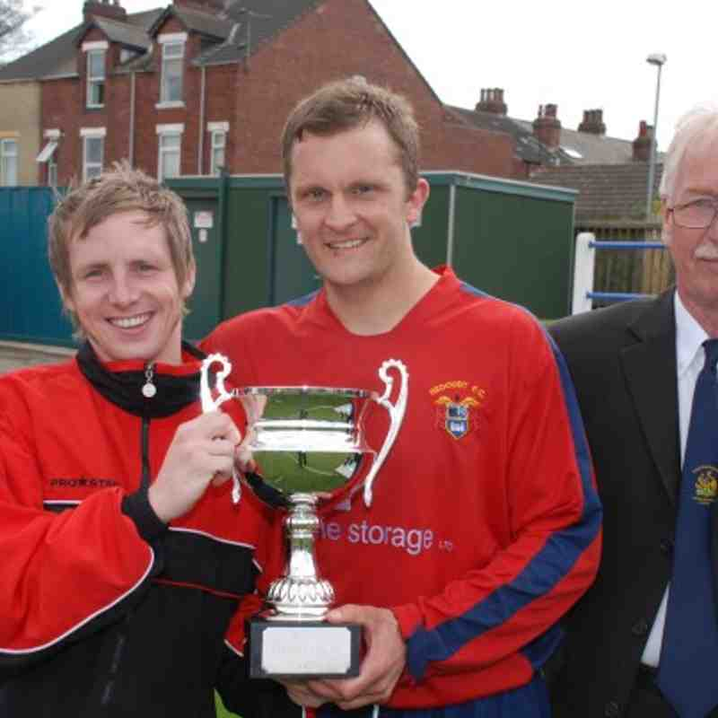 LMC Member Mr. T. Whelan presents Redoubt's Clifton Firth and skipper Mark Alvey with the Premiership Cup.