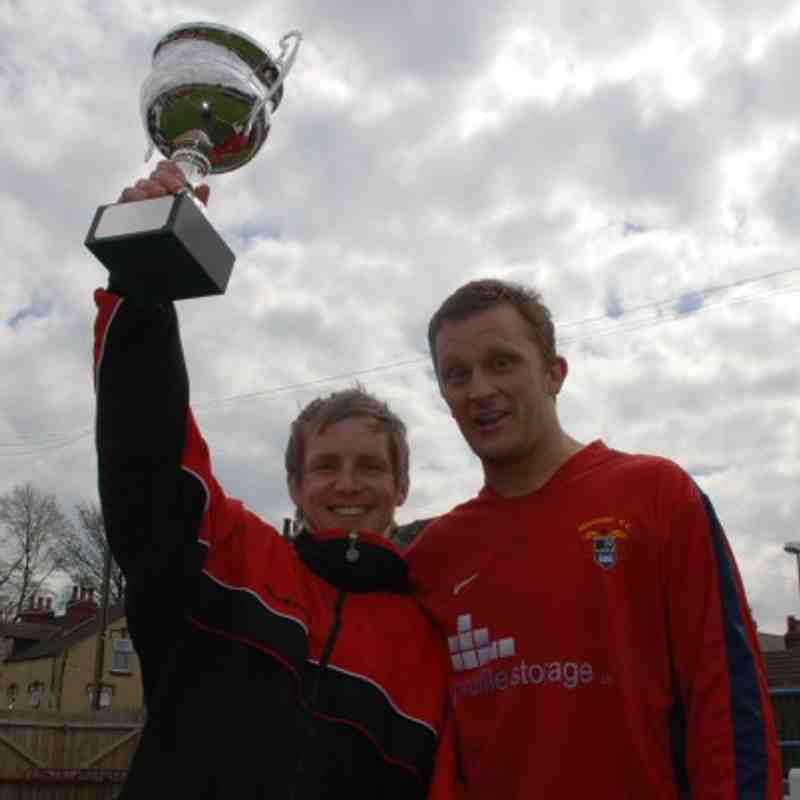 Clifton Firth and skipper Mark Alvey lift the Premier Division Cup.