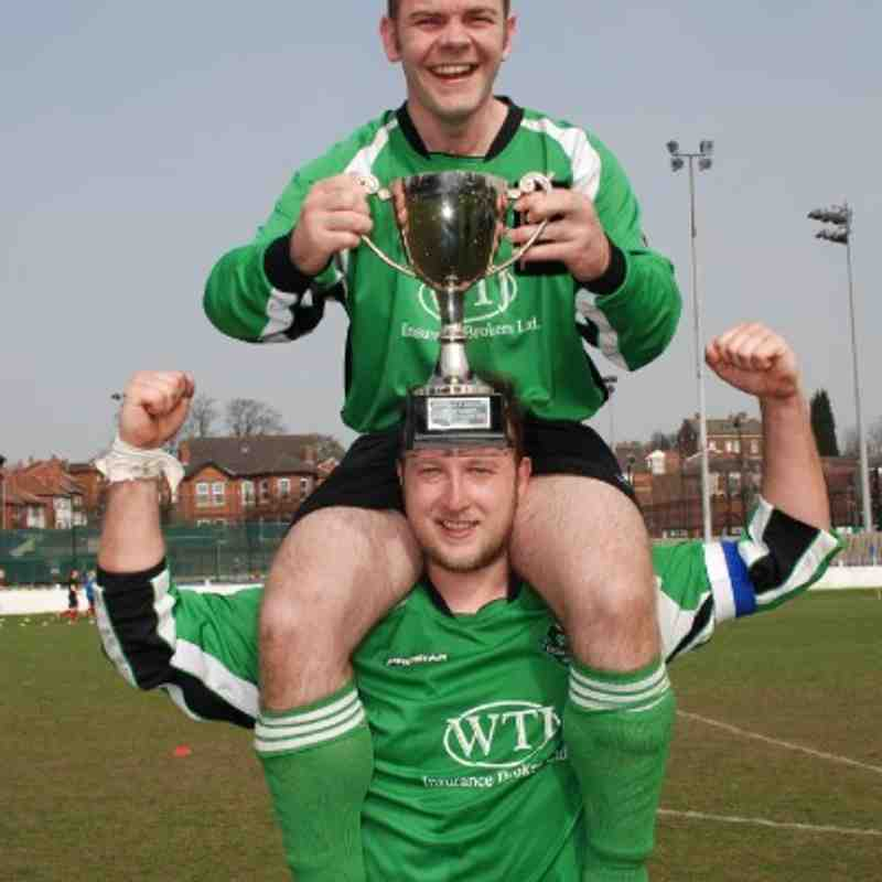 Carr Gate's Dave Woollin carries the Division Four Cup on his head with a little help from skipper Chris Bragg!