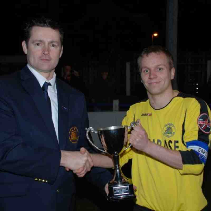 W&DSFL Chairman Mr. Adie Wilkinson presents the Division Three League Cup to Fleece Reserves skipper Matthew Patterson.