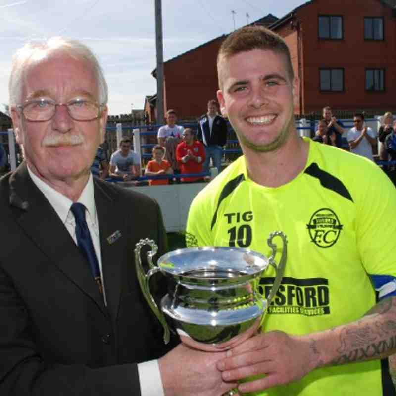 Registration Secretary Terry Whelan presents the Premier Division Cup to a delighted Tom Clarke, Hemsworth Miners Welfare captain.