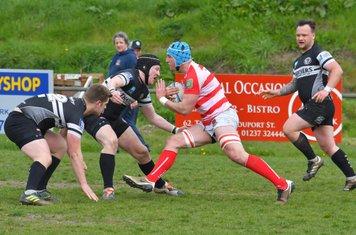 Winscombe fly-half Jim Merryfield braces for a tackle on Bideford flanker Jono Mock