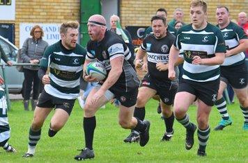 Winscombe lock Luke Fisher breaks through the Saracens defence