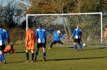 Players look on as Lewis Dench's first goal for the club goes in to reduce the deficit to one.