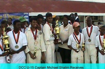 DCC U-15 Captain Michael Shalim Receives The Cup From Ms Collette Jordan of Brainstreet.