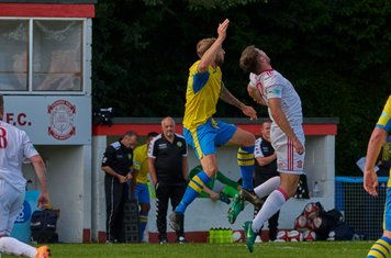 Tom Maddison and Harry Millard jumping for the ball.