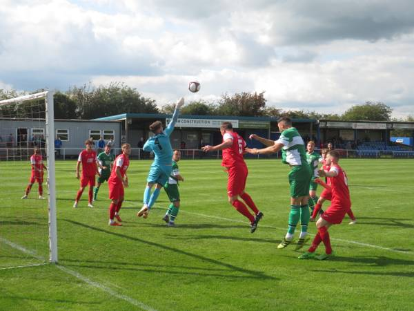 Ash Rawlins clawing the ball away from goal.