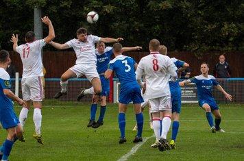 Harry Millard heading a cross goalwards.
