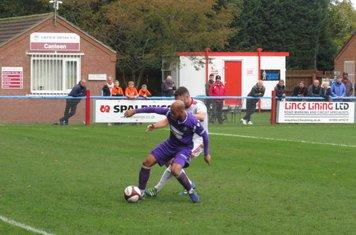 Rhys Thompson under pressure from Matt Wilson.