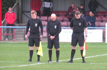 The officials observing a minute's silence.