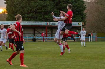 Jamie Goddard and Oli Donald jumping for a header.