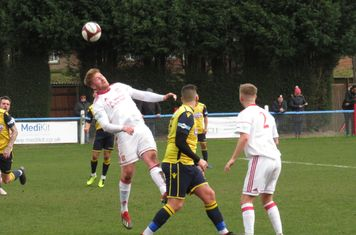 Mark Gray leaning back to head the ball.
