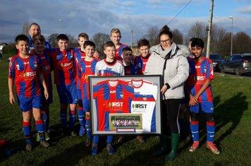 U13s make a presentation of framed shirts to sponsors Hirst Electrical