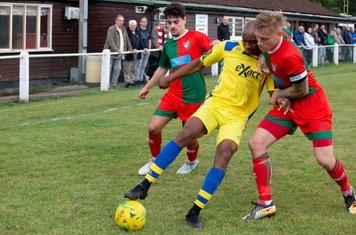 Luke Elliott has a hold of John Ufuah as Whitstable supporters look on