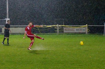 Aaron Millbank scores from the spot in the driving rain