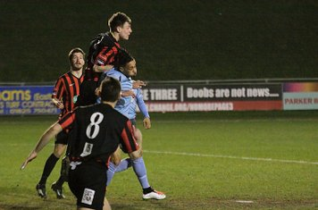 George Brown heads clear from Enfield's Corey Whitely (blue)