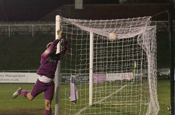 Lewes keeper Rikki Banks covers his post as a cross drops onto the roof of the net