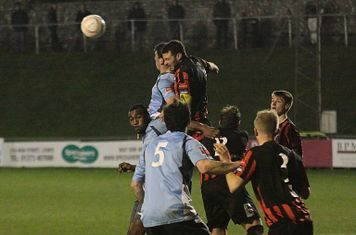 Lewes skipper Gary Elphick (red/black) heads clear from Claudiu Vilcu