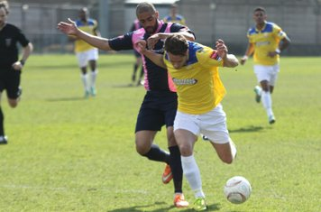 Enfield's Joe Stevens (yellow) challenged by Ashley Carew