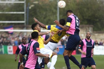 Dulwich's Ethan Pinnock (pink/blue 6) challenges Stanley Muguo