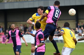 Enfield's Claudiu Vilcu (yellow, L) challenges Ethan Pinnock