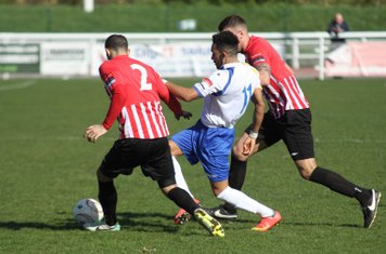 Enfield's Tyler Campbell tries to find a way between Danny Woodards (L) and Danny Johnson