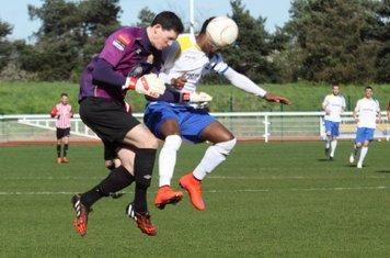 Hornchurch keeper Sam Mott heads clear from Bobby Devyne