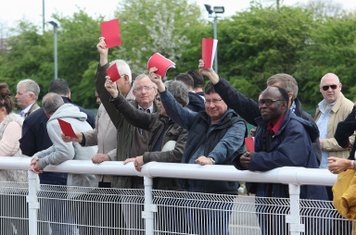 Enfield supporters show red cards in protest at the FA's decision to find the club guilty of playing an ineligible player earlier in the season