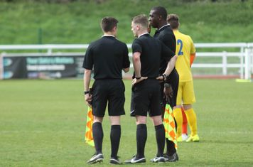 The match officials confer, resulting in  a red card for Enfield's Joe Ellul