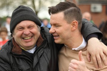 Enfield Manager Bradley Quinton (R) celebrates with a supporter