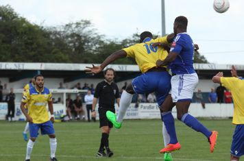 Billericay's Ola Williams (R) heads clear from Alex Cathline