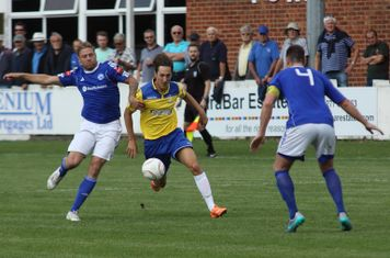 Enfield's Jake Hutchings (yellow) challenged by Jamie Guy