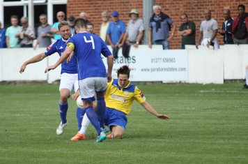 Enfield's Jake Hutchings (yellow) challenged by Jamie Guy (L) and Frank Curley
