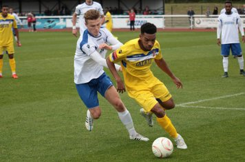 Staines's Michael Kalu (R) under pressure from Mickey Parcell