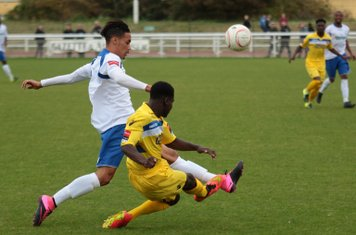 Staines's Erivaldo Felix (yellow) clears from Corey Whitely