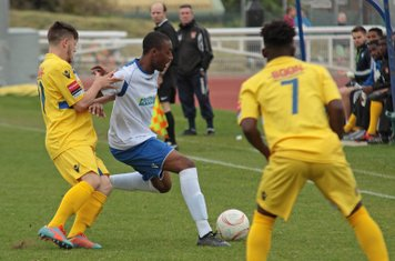 Staines's Jack Hutchinson (yellow, L) challenges Ricky Gabriel