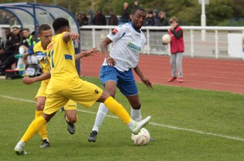 Staines's Ashley Lodge (rear) and Michael Kalu challenge Ricky Gabriel
