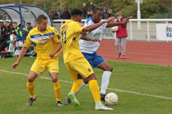 Staines's Michael Kalu (11) challenges Ricky Gabriel