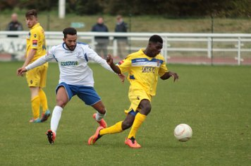 Staines's Erivaldo Felix (R) clears from Tyler Campbell