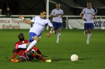 Enfield's Corey Whitely hurdles a challenge from Dave Diedhiou