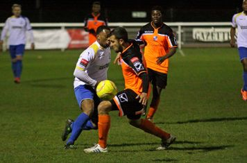 Enfield's Vance Bola (white) plays thew ball past Ahmet Rifat
