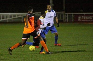 Wingate's Ola Sogbanmu (orange) and Enfield's Vance Bola and Jandir da Cruz (R)