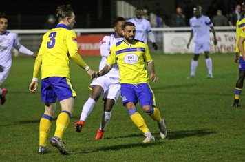 Kingstonian's Tyron Smith (yellow, R) beats Bobby Devyne to the ball