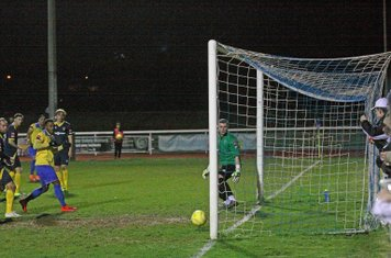Corey Whitely's (yellow, background) shot creeps in at the far post for the first Enfield goal