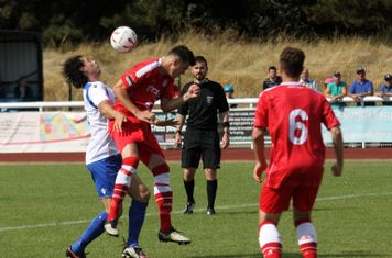 Harrow's Harry Newman (red) wins a header against Harry Ottaway