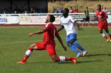 Harrow's Shaun Preddie (red) clears from Kelvin Bossman
