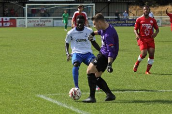 Harrow keeper Luke Williams wins a race to the ball ahead  of Kelvin Bossman