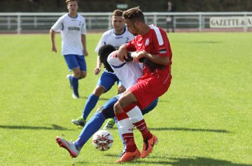 Enfield's Kelvin Bossman tries to spin away from Josh Webb (red)