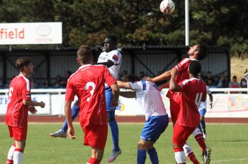 Enfield's Kelvin Bossman (white, L) flicks the ball on at a set piece
