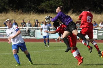 Harrow's keeper Luke Williams holds onto the ball despite crashing into his teammate Shaun Preddie